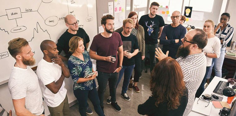 equipe de outsourcing de TI reunida em frente à um quadro debatendo ideias