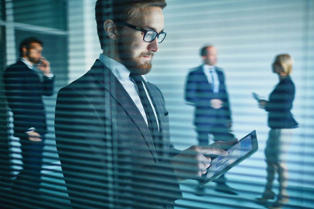 executivo usando seu tablet atrás de um vidro