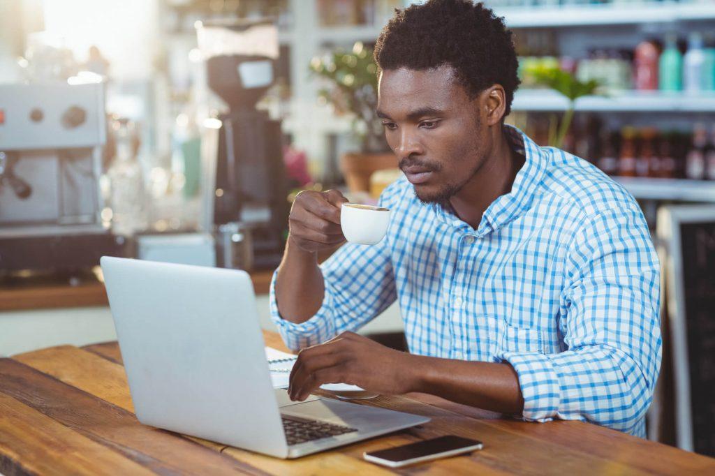 profissional tomando um café enquanto usa seu laptop