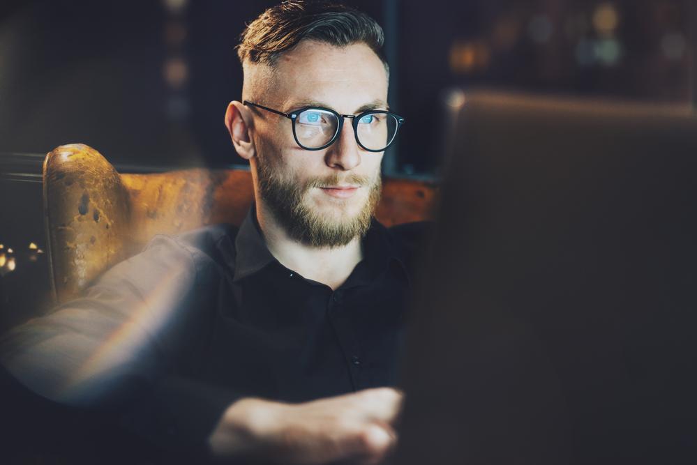 profissional de frente para o notebook, com a imagem refletida em seus óculos