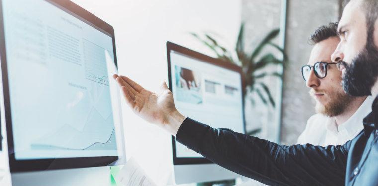 Executivo mostrando informações de governança de ti em um monitor