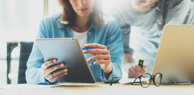 profissionais analisando dados num tablet