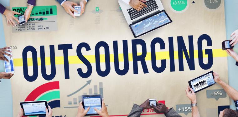 Mesa com várias pessoas analisandos dados do outsourcing de ti