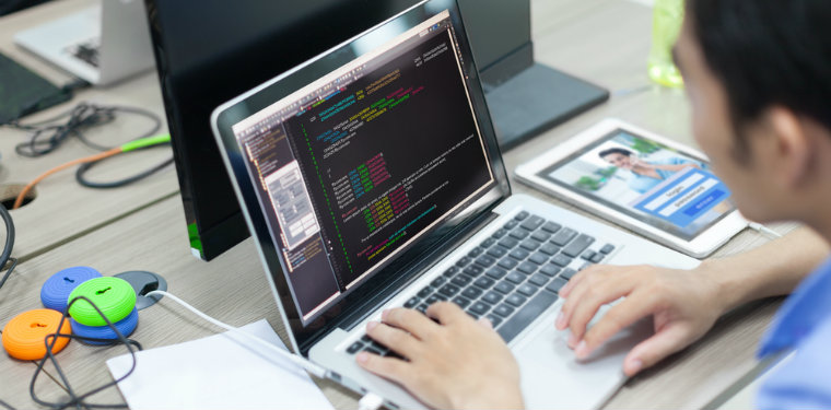 profissional analisando linhas de código. Um dos grandes desafios do outsourcing de TI