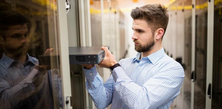 trabalhador alterando equipamentos num servidor graças a sua capacitação da equipe de TI.