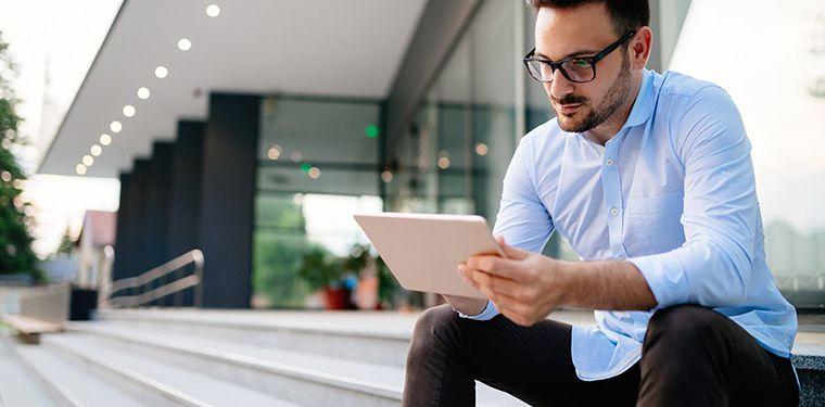 Homem sentado em uma escada enquanto lê um artigo em seu tablet. Representação de estudo sobre arquitetura em TIC.
