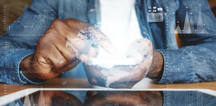 Homem usando seu celular enquanto uma luz formando um holograma de um mundo conectado sai de sua tela ilustrando a transformação digital.