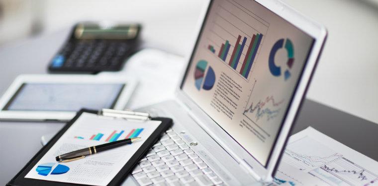 notebook e tablet em cima de uma mesa com gráficos abertos representando uma análise de impacto no negócio
