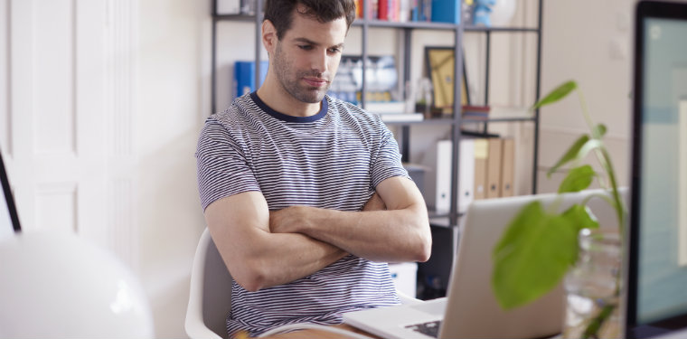 profissional em frente ao seu notebook pensando em maneiras de usar o design thinking na TI