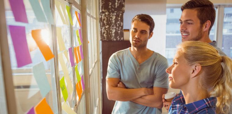 equipe observando post its num quadro. prática muito recomendada no gerenciamento de mudanças