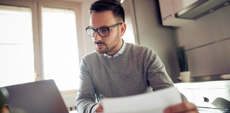 Profissional olhando a tela de seu notebook enquanto segura uma folha de papel. Representação de um planejamento estratégico