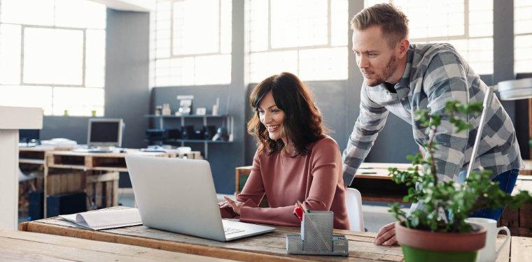 Dois profissionais olhando a tela de um notebook. Representação do uso do Hashgraph