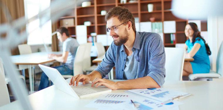 Um gerente de projetos sentado em sua mesa enquanto olha para o seu notebook