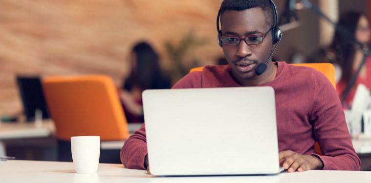 Profissional de Service Desk sentado em frente ao seu notebook.