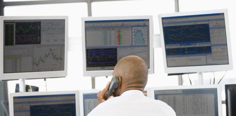 Operador de NOC em frente à várias telas de monitoramento