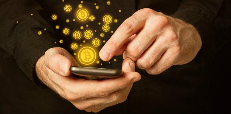 pessoa usando seu celular. enquanto sua mão clica na tela, moedas de bitcoin são lançadas para fora do aparelho, representando o mundo do blockchain e hashgraph