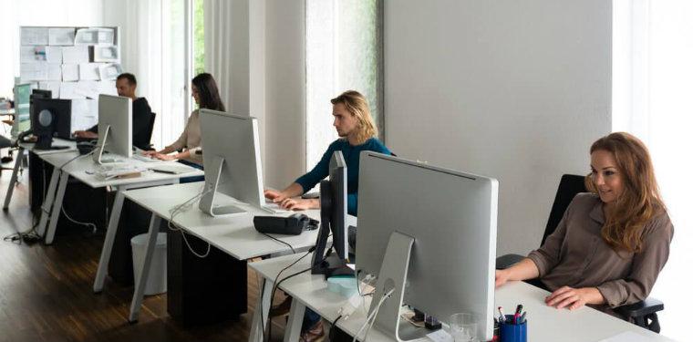 Equipe de cibersegurança atuando em frente seus computadores.