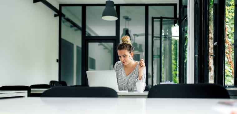 mulher sentada em frente ao seu notebook em uma mesa. representação da pesquisa por certificações de TI