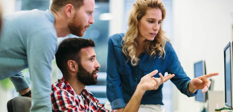 equipe de outsourcing de TI olhando para a tela de um computador