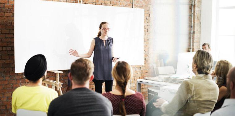 Instrutora de ISO 20000 em pé em frente à uma turma de alunos.