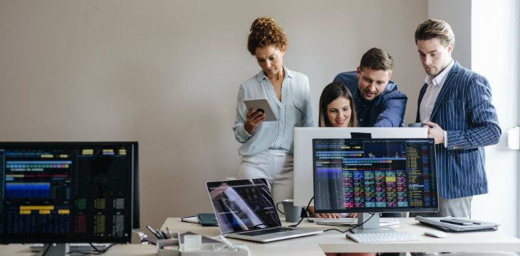 Equipe fazendo a gestão de problemas enquanto todos se concentram em uma tela e uma das analistas verifica dados em seu celular.