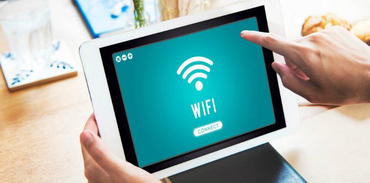"""Pessoa segurando um tablet com a tela aberta com o ícone de """"WIFI"""", menção a segurança de rede wifi"""