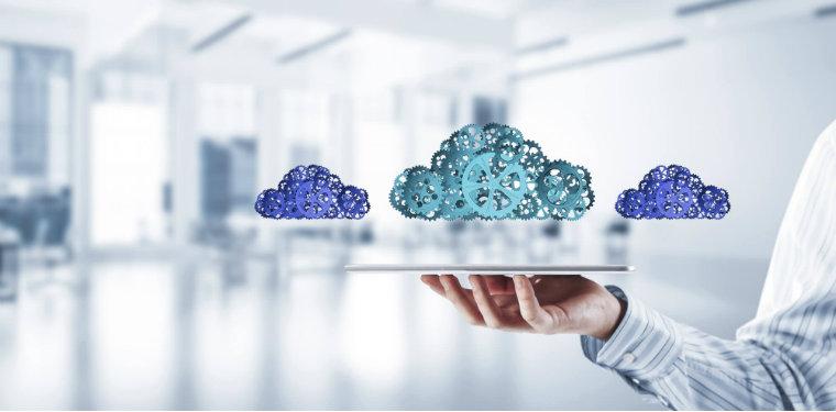 3 nuvens formadas por engrenagens flutuando em cima de um tablet segurado por uma pessoa.