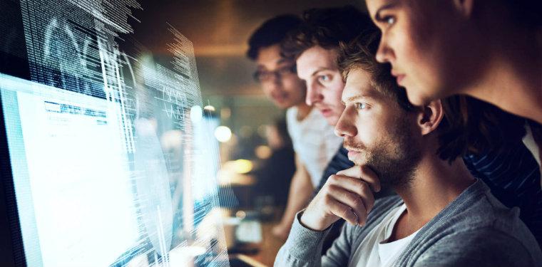 Equipe de transformação digital observando um monitor luminoso.