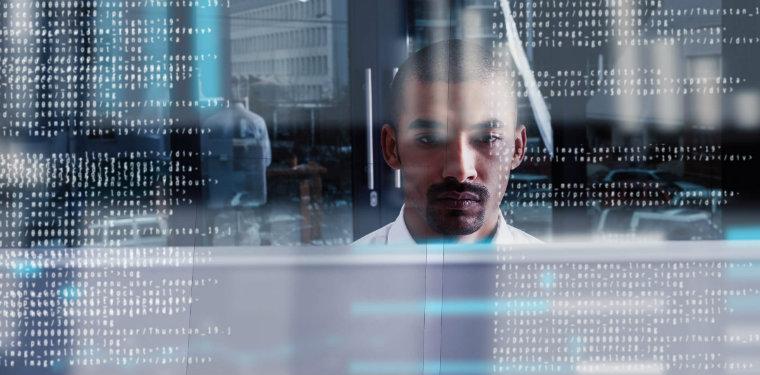 Profissional sentado em frente ao seu computador enquanto um reflexo de dados fica à sua frente.