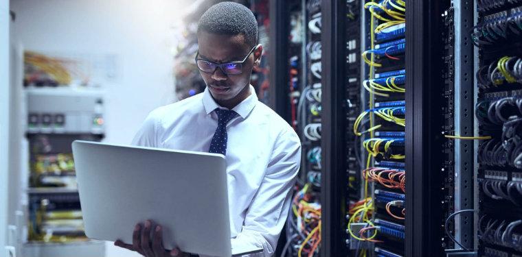Homem usando seu notebook em frente à racks de um data center