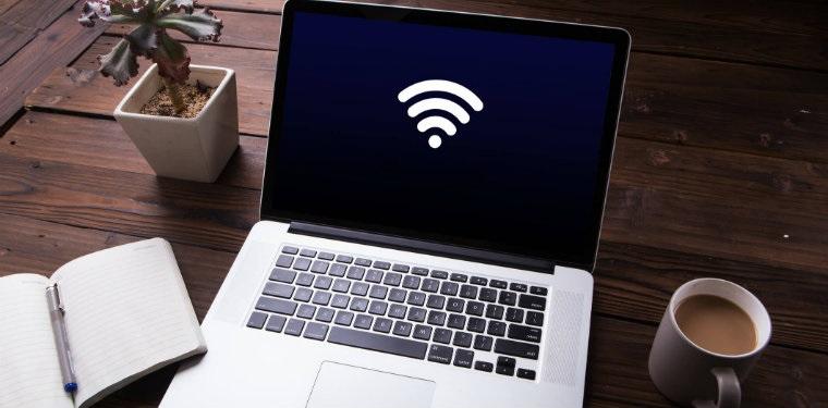 Computador em uma mesa de madeira com um caderno de anotações aberto e uma xicará de café. Símbolo de wifi na tela do computador