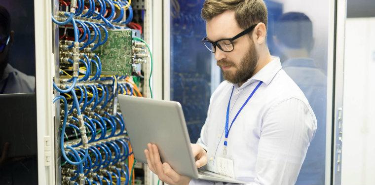 Homem usando óculos fazendo alterações em um rack, exemplo de gestão de data centers.