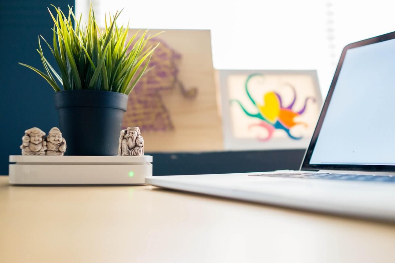 Mesa com laptop aberto e ligado ao lado de um pé de plantas verdes e algumas miniaturas de esculturas medievais