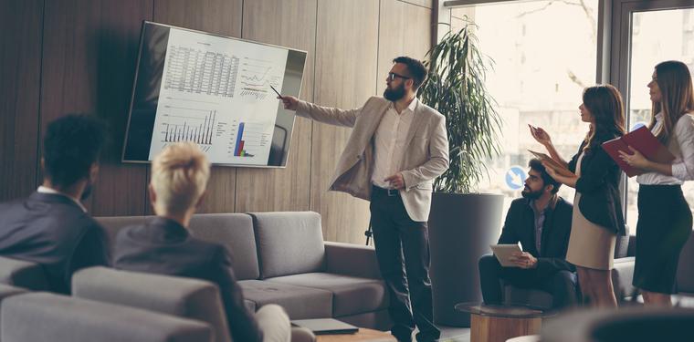 Grupo de trabalho olhando para uma tela com um dashboard da gestão de ativos da empresa
