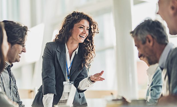 mulher sorridente bem vestida no meio de uma mesa com pessoas a observando no ambiente de trabalho. referência a execução de processos organizacionais