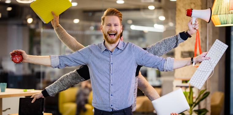 Homem sorrindo com os braços abertos enquanto atrás dele, vários braços seguram objetos. Referência a Serviços gerenciados de TI