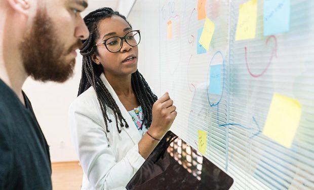 Dois profissionais observando um quadro de vidro com postits colados. Referência a criação de um roadmap.