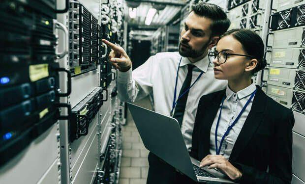 dois profissionais analisando um data center. Alusão a um possível tratamento de um chamado de Gestão de Incidentes de TI