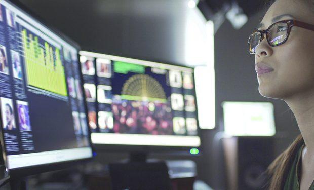 Mulher atenta olhando as telas de seu command center
