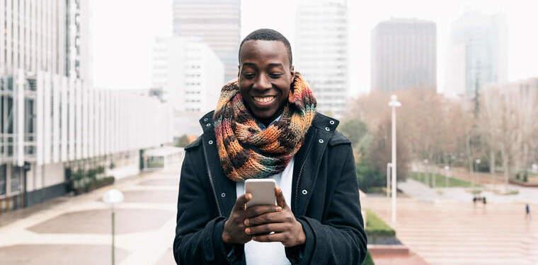 Mulher sorridente caminhando olhando para seu celular. Imagem mostra a boa experiência do cliente graças a segurança de dados