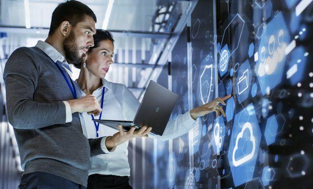 Profissionais em frente a um Rack de rede com os símbolos de uma nuvem, de um escudo e de uma bateria. Representação da prática dos serviços gerenciados de TI