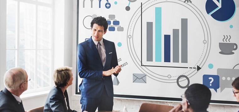 homem de terno apresentando um quadro com gráficos para uma equipe de TI. Representação da aplicação do COBIT 2019